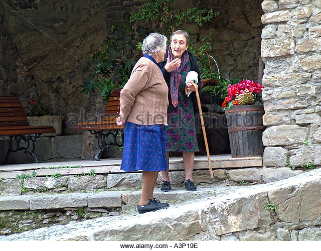 two-old-women-stopping-for-an-evening-chat-in-small-italian-hill-town-a3p19e
